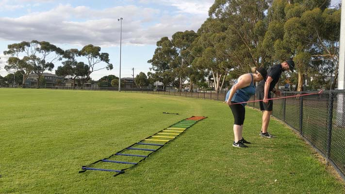 Client training outside with her south melbourne personal trainer.