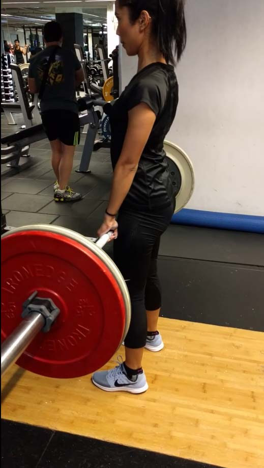 Beginner female client learning how to lift heavy without injury.