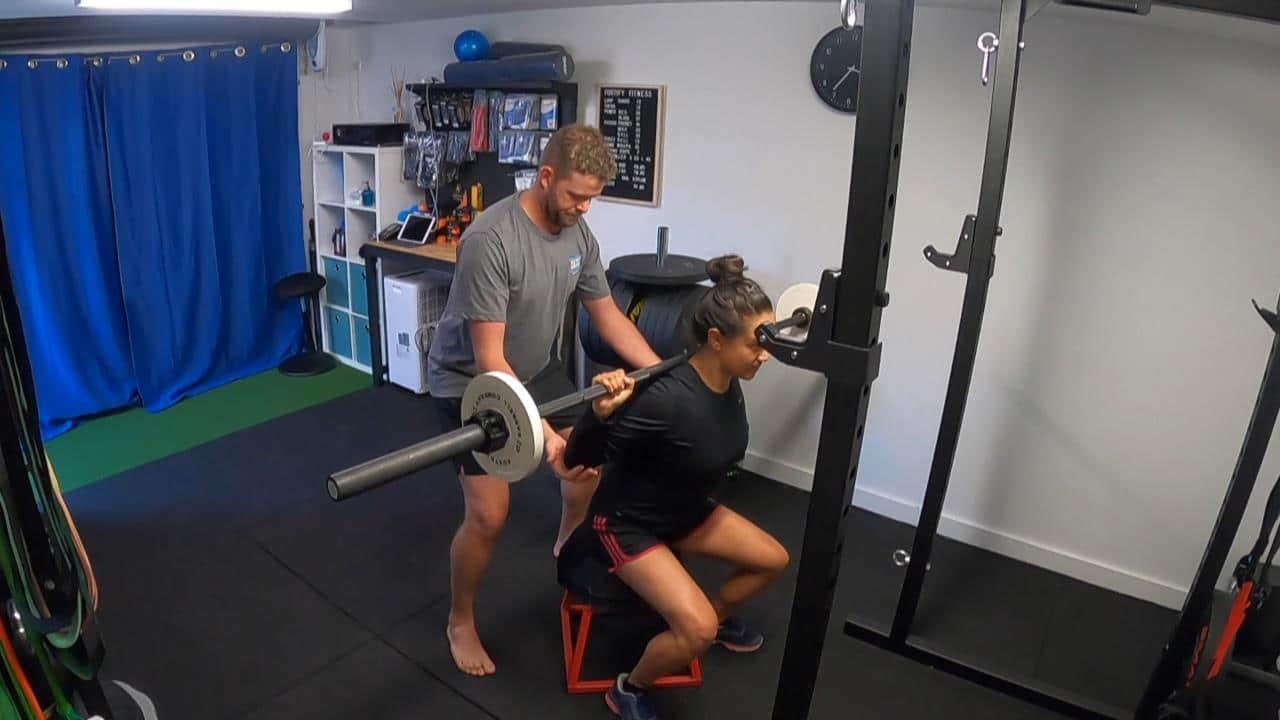 Matt spotting client on the box squat at his Williamstown personal training studio